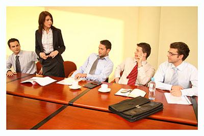 אנשים בשולחן ישיבות אשה עומדת